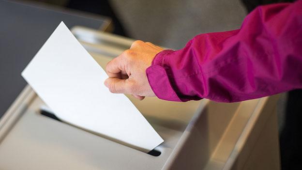 Ein Wähler wirft sein Kuvert in die Wahlurne.