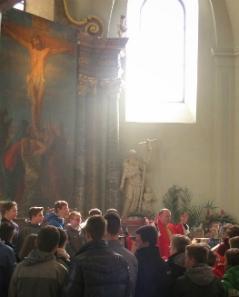 Altarbild mit Jesu Tod und die feiernde Gemeinde mit Palmzweigen um den Altar