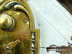 Ein goldenes Schloss einer herrschaftlichen weißen Tür