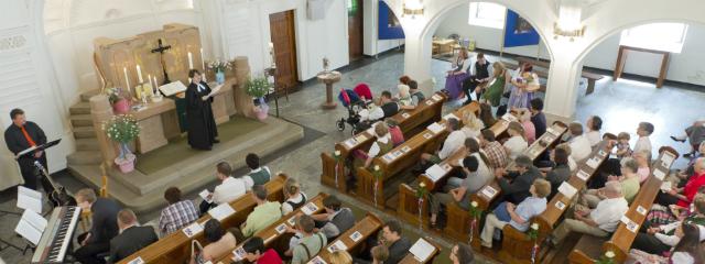 Kirche während eines Gottesdiensts von der seitlichen Empore aus, Pfarrerin am Altar, Musiker an der Seite