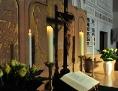 Altarkreuz mit seinem Schatten neben der Heiligen Schrift und gelben Rosen am Leobener Altar