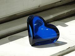 Ein blaues gläsernes Herz liegt auf einem Fensterbrett