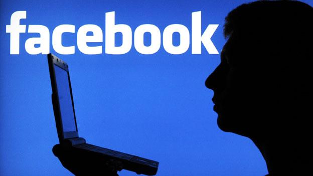 Silhouette eines Mannes vor einem Facebook-Logo