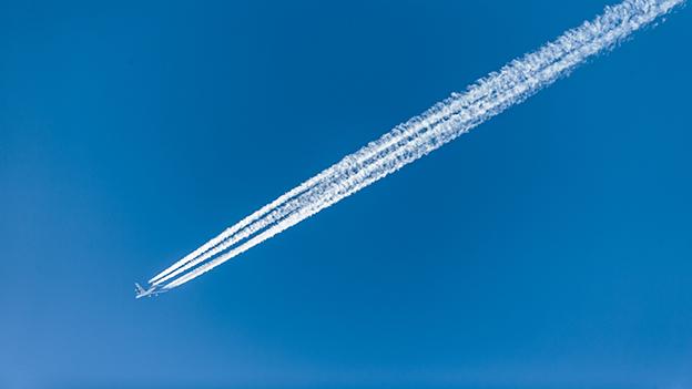 Kondensstreifen und ein Flugzeug am Himmel