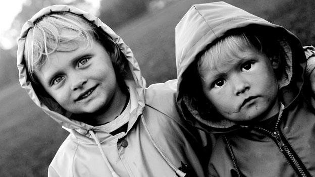 Zwei Kinder mit Regenjacken