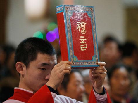 Ein chinesischer Ministrant hält die Bibel während einer Weihnachtsmesse in Peking hoch