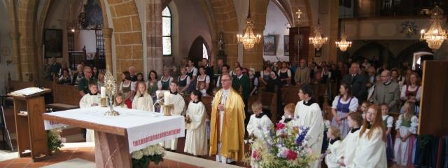 Pfarrer, Ministrantinnen, Ministranten und Gemeinde vor dem Altar, geschmückte Kirche