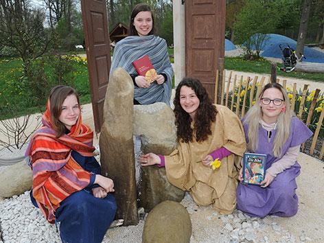 """Mädchen in historischen Gewändern vor einem Brunnen im """"Bibelgarten Tulln"""""""