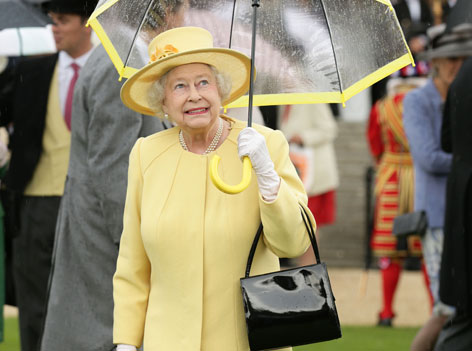 Die Queen in einem gelben Kleid mit Regenschirm bei einer Gartenparty
