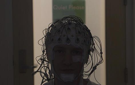 Einer der Studienteilnehmer beim EEG mit zahlreichen Elektroden auf seinem Kopf
