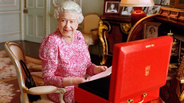 Portrait der Queen vor einem roten Koffer sitzend