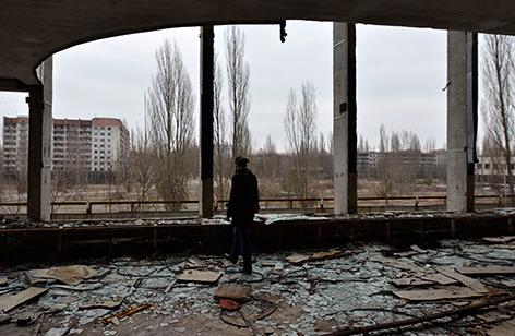 Szene aus der Geisterstadt Prypiat 2011: Ein Mensch steht in einem verfallenen Haus