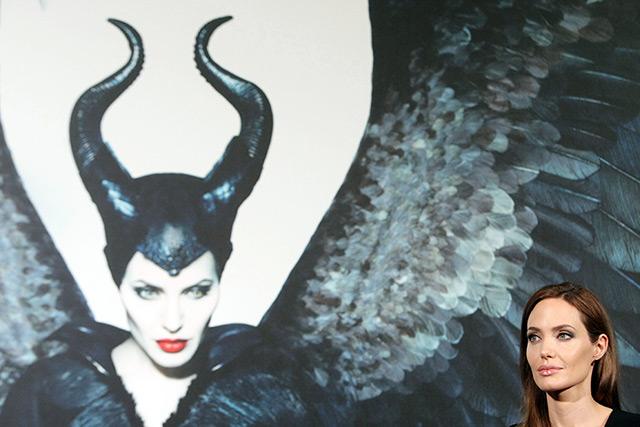Die Schauspielerin Angelina Jolie im Vordergrund, dahinter eine Einblendung des Films Maleficent, in dem sie eine böse Fee spielt