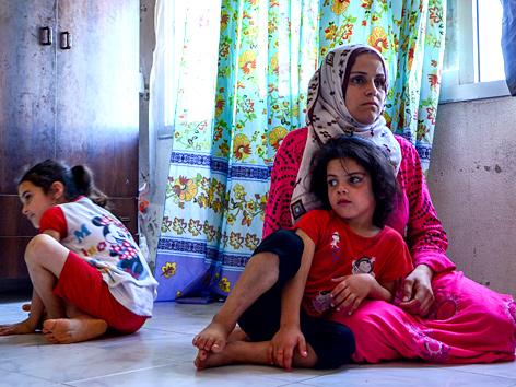 Eine Frau mit zwei Kindern in einer Notunterkunft im Nordlibanon