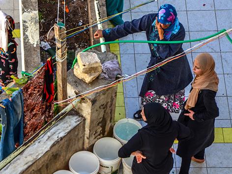 Frauen in einer Notunterkunft im Nordlibanon stehen im Wasser an