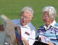Pensionistenpaar auf einer Bank mit Landkarte in der Hand