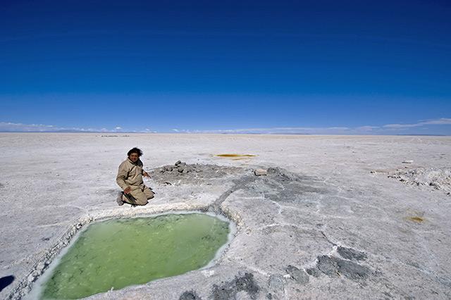 Mann kniet vor Sole in bolivischer Salzwüste