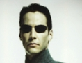 Filmausschnitt aus Matrix mit Figur Neo im Hintergrund, davor 2 Menschen im Schattenriss