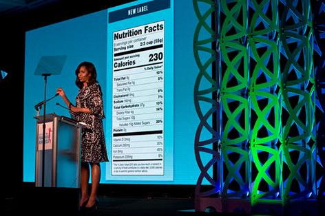 Michelle Obama auf der Bühne, im Hintergund ein projiziertes Fodd label