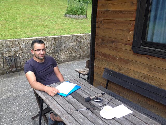 Abdalla Mohammad sitzt an einem Holztisch im Freien