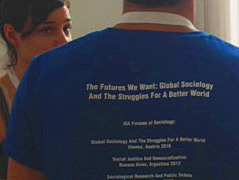 "2 Studierende beim Kongress, der eine steht mit dem Rücken zur Kamera, man kann den Schriftzug der Veranstaltung lesen ""The futures we want: global sociology and the struggles for a better world"""