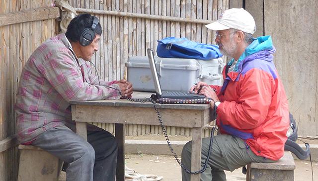 Wissenschaftler spielt einem Mann vom Stamm der Tismane Hörproben auf einem Kopfhörer vor