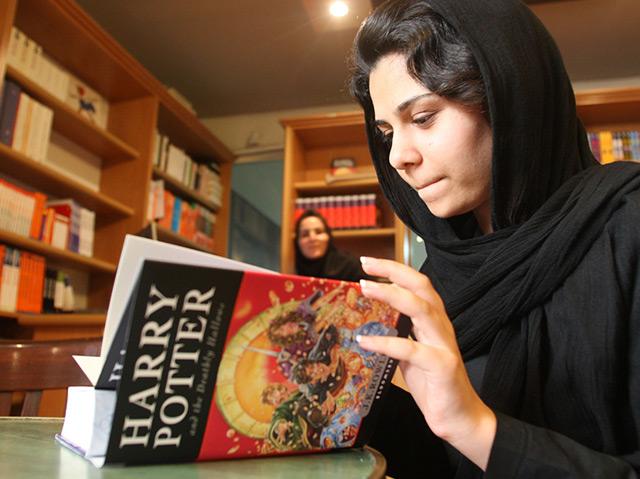 Eine Frau mit Kopftuch im Iran liest ein Buch von Harry Potter