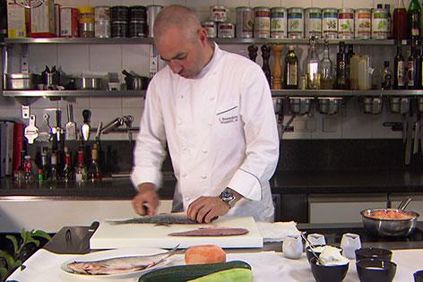 Johannes Brandstätter filetiert Fisch in der Küche