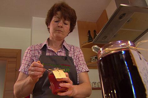 Maria Schlager-Haslauer mit Marmeladeglas und Löffel