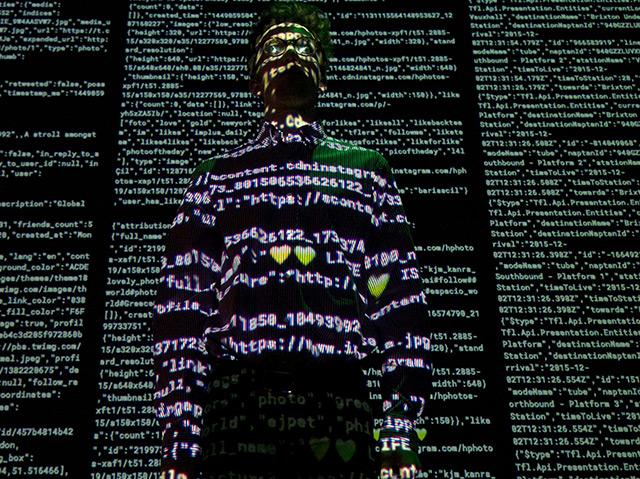 Teil einer britischen Kunstausstellung: In einem dunklen Raum wird ein Mann von weißen Zahlencodes angstrahlt, die aus dem Internet stammen