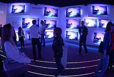 Menschen informieren sich auf der Elektronikmesse IFA in Berlin auf dem Stand des Unternehmens Philips im Bereich Fernsehgeräte