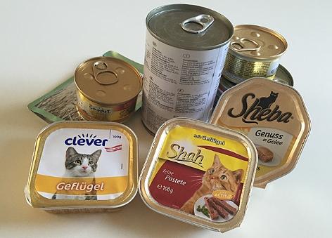verschiedene Dosen, Säckchen und Schalen mit Katzenfutter