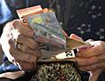 Eine Pensionisten kramt aus einer Geldbörse Euroscheine hervor