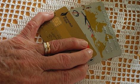 Hand eines alten Menschen und Kreditkarten