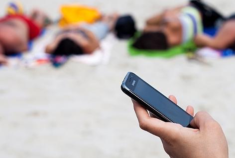 Eine Frau am Strand tippt auf ihrem Mobiltelefon, im Hintergrund liegen Sonnenbadende