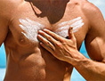 Ein Mann cremt sich mit Sonnencreme ein