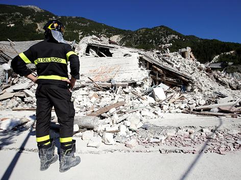 Feuerwehrmann vor Trümmern nach Erdbeben in Pescara del Tronto, Italien