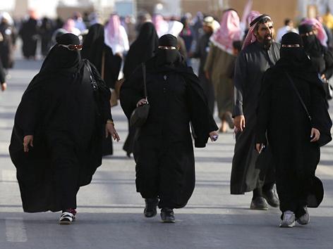 Drei Frauen in Nikabs auf einer Straße in Saudi-Arabien