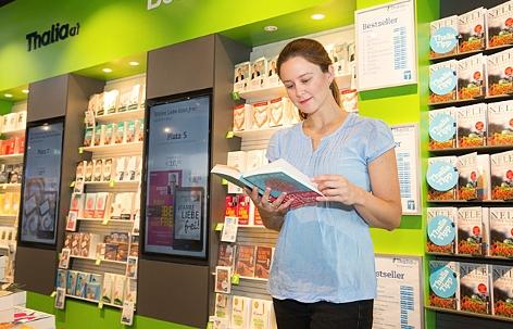 Eine Frau blättert in einer Thalia-Filiale in einem Buch