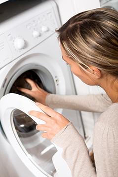 Frau befüllt Waschmaschine