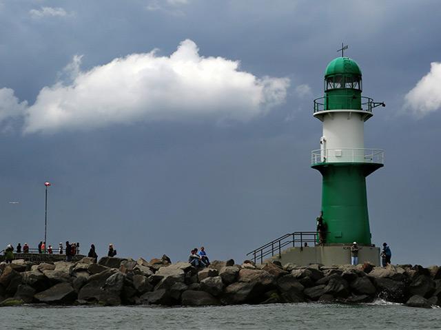 Ostsee vor Warnemünde: Wolken ziehen über einem grünen Leuchtturm durch, die in der Sonne vor dem dunklen Himmel hell leuchten