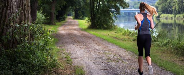 Joggerin läuft einen Waldweg entlang