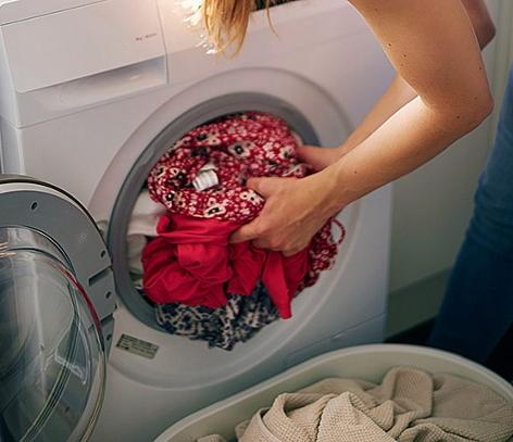 Frau gibt Schmutzwäsche in die Maschine