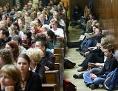 Studierende sitzen in einer Vorlesung am Boden.