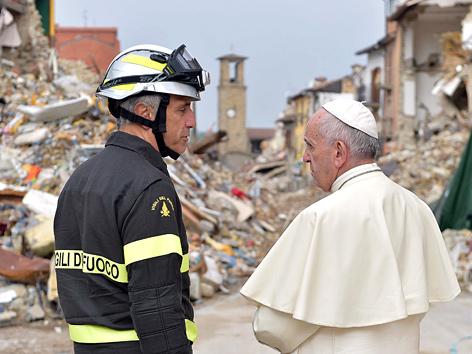 Papst Franziskus mit einem Feuerwehrmann beim Besuch in Amatrice