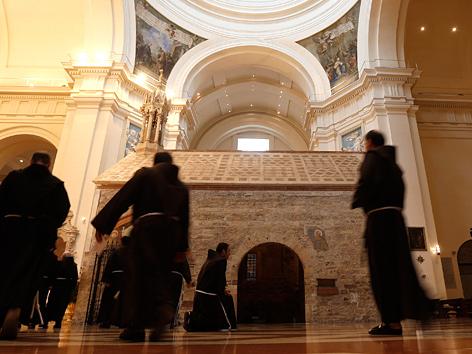 Franziskaner-Patres gehen an der Portiuncula-Kapelle vorbei