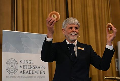 Physiker Thors Hans Hansson hält schwedisches Gebäck in der Hand