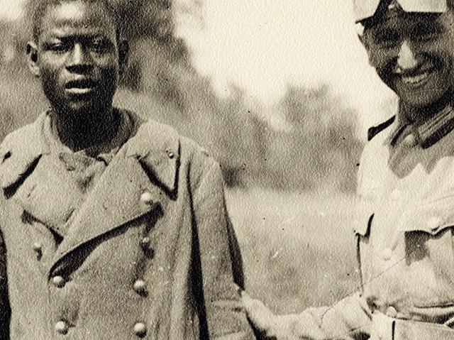 Deutscher Soldat führt einen Kriegsgefangenen der französischen Kolonialtruppen vor