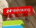 Schilder an einer Bankfiliale verweisen auf 24-Stunden-Banking und einen Bankomat
