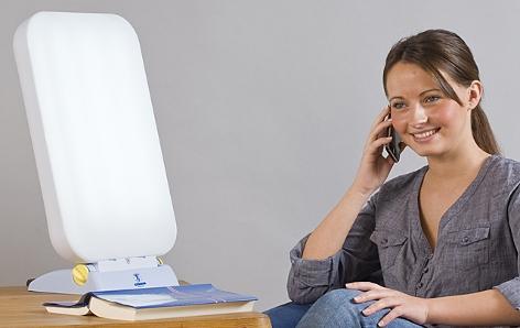 Frau sitzt vor Lichttherpaiegerät und telefoniert